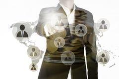 La doppia esposizione del punto dell'uomo di affari il dito rappresenta il gruppo principale e le monete dorate in barattolo, con Immagini Stock Libere da Diritti