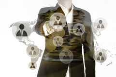La doppia esposizione del punto dell'uomo di affari il dito rappresenta il gruppo principale e le monete dorate in barattolo, con Fotografia Stock