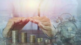 la double exposition de la main deux protègent la pile des pièces de monnaie et de la ville d'argent Photo stock