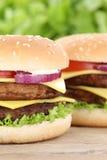La double fin de plan rapproché d'hamburger de cheeseburger vers le haut des tomates de boeuf a laissé Photographie stock libre de droits