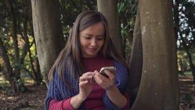 La douce fille est assise près de l'arbre dans le parc elle utilise un smartphone et sourit clips vidéos