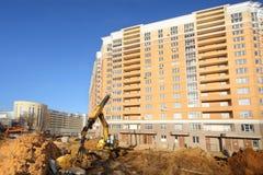 La draga scava l'alta costruzione multipiana vicina a terra Fotografia Stock Libera da Diritti
