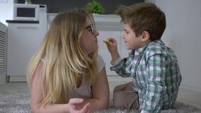 La dulzura maternal, el niño feliz con la madre que come la comida y la frotación sospecha la mentira en piso dentro almacen de video