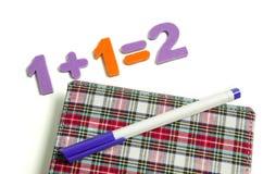 La ecuación de números coloreados al lado de una libreta en una jaula y un bolígrafo foto de archivo