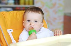 La edad del bebé de 11 meses come las frutas usando la recortadora de chapas Fotos de archivo