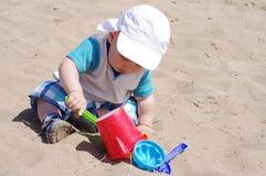 La edad del bebé de 9 meses juega con la arena Imagenes de archivo