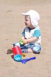 La edad del bebé de 9 meses juega con la arena en la playa Fotografía de archivo libre de regalías