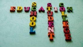 La educación de las palabras, escuela, estudiante, universidad construida de letras de madera coloridas en una tabla ligera imagen de archivo