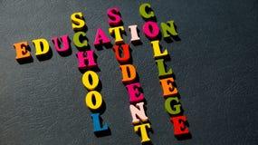 La educación de las palabras, escuela, estudiante, universidad construida de letras de madera coloridas en una tabla oscura foto de archivo libre de regalías