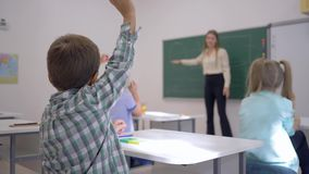La educación de los niños, alumnos en la lección escucha el profesor en la pizarra en enfocado en la sala de clase de la escuela almacen de video