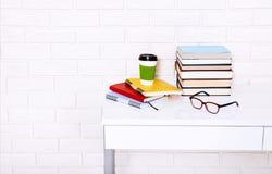 La educación reserva la literatura y los cuadernos con los accesorios en lugar de trabajo cerca de la pared de ladrillo Visión su Fotografía de archivo