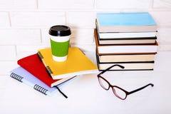 La educación reserva la literatura y los cuadernos con los accesorios en lugar de trabajo cerca de la pared de ladrillo Visión su Imagen de archivo