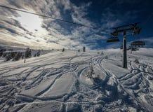 La elevación de silla le toma a través del área del esquí con los cielos azules y las cuestas blancas fotos de archivo libres de regalías