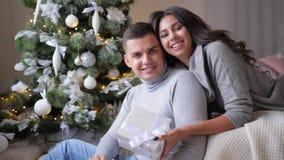 La emoción de la felicidad, muchacha con el regalo de Navidad abraza su marido y la mirada en la cámara en fondo de almacen de metraje de vídeo