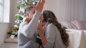 La emoción de la felicidad, nieve artificial cae en dos amantes que se sientan en piso en el cuarto cerca de árbol del Año Nuevo metrajes
