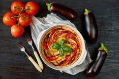 La empanada con las berenjenas y los tomates en el plato de la hornada adornado con albahaca fresca se va Tarta vegetal hecha en  foto de archivo libre de regalías