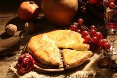 La empanada con queso sometió con el vino, uvas y una granada Imagenes de archivo