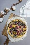 La empanada de arándano hecha en casa en un tablero de madera con algodón florece en un fondo gris imagen de archivo