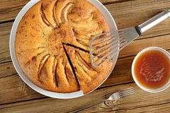 La empanada de manzana hecha en casa cortó con la espátula, la bifurcación y la taza de té Fotografía de archivo libre de regalías