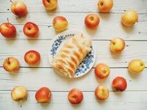 la empanada de manzana hecha en casa en una placa y las manzanas amarillas y rojas están en los tableros blancos Imagenes de archivo
