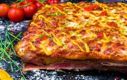 La empanada de pizza hecha en casa de la carne con tocino cortó el primer en la tabla visión horizontal desde arriba imagen de archivo