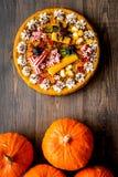 La empanada hecha en casa para Halloween adornó arañas gomosas entre las calabazas en copyspace de madera de la opinión superior  Fotos de archivo