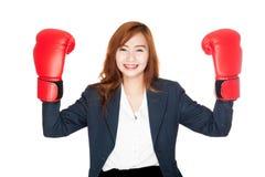 La empresaria asiática con el guante de boxeo le muestra los puños Foto de archivo libre de regalías