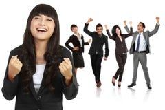 La empresaria asiática joven con su equipo detrás, hace un éxito g Imagenes de archivo