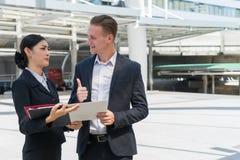 La empresaria asiática que lleva a cabo el documento a mano y habla de futuro del negocio con el hombre de negocios caucásico imagen de archivo