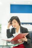 La empresaria (asiática) tailandesa de la tensión está leyendo su fichero de documento i fotografía de archivo libre de regalías