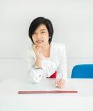 La empresaria (asiática) tailandesa linda está trabajando con su fil del documento Foto de archivo libre de regalías