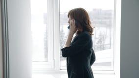 La empresaria atractiva está hablando en el teléfono por la ventana en oficina moderna almacen de video