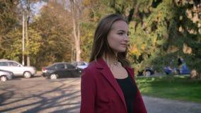 La empresaria atractiva joven camina con confianza en la calle, sacando las gafas de sol del theior y la sonrisa metrajes