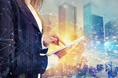 La empresaria comparte el documento con la tableta efecto del Internet sobre fondo imagen de archivo