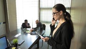 La empresaria comunica por el teléfono con los clientes durante la reunión en la cámara lenta almacen de video