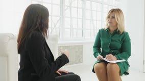 La empresaria con el ataque de nervios habla al psicólogo que toma notas almacen de metraje de vídeo