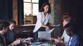 La empresaria confiada está dando los papeles con la información visual a su equipo creativo y está hablando en la reunión en ofi metrajes