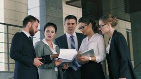 La empresaria confiada que lleva los documentos con los gráficos discute sus proyectos con sus colegas almacen de video