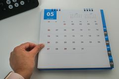 La empresaria control calendario de mayo de 2018 en la mano izquierda para recuerda la reunión y la cita Foto de archivo libre de regalías
