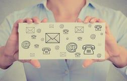 La empresaria da el correo de los iconos del contacto de tarjeta, correo electrónico, teléfono del web Imagenes de archivo