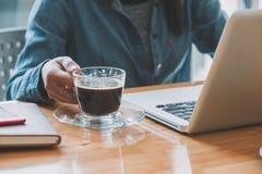La empresaria da sostener las tazas de café y usar el ordenador portátil foto de archivo