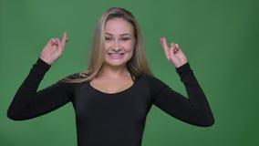La empresaria en blusa negra que gesticula los cruzar-fingeres firma para mostrar esperanza en cámara en el fondo verde almacen de video