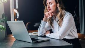 La empresaria en la camisa blanca se está sentando en oficina en la tabla delante del ordenador y mira pensativamente la pantalla fotografía de archivo