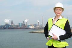 La empresaria en el casco de protección y la seguridad conceden sostener un tablero al aire libre Foto de archivo