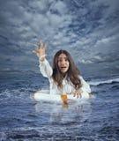 La empresaria en el océano con el flotador pide ayuda durante una tormenta fotos de archivo libres de regalías
