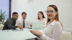 La empresaria enrolla la pantalla de la tableta y sonríe mientras que preraring para la presentación almacen de video