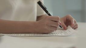 La empresaria escribe en un documento en su oficina almacen de video