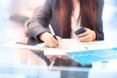 La empresaria escribe en un documento en su oficina Imagen de archivo libre de regalías