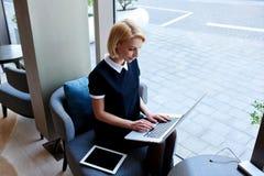 La empresaria está comprobando el email en Internet vía el red-libro portátil durante descanso para tomar café en café Imagen de archivo libre de regalías