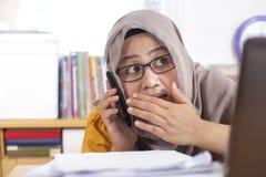 La empresaria está hablando secretamente en el teléfono en el trabajo imagen de archivo
